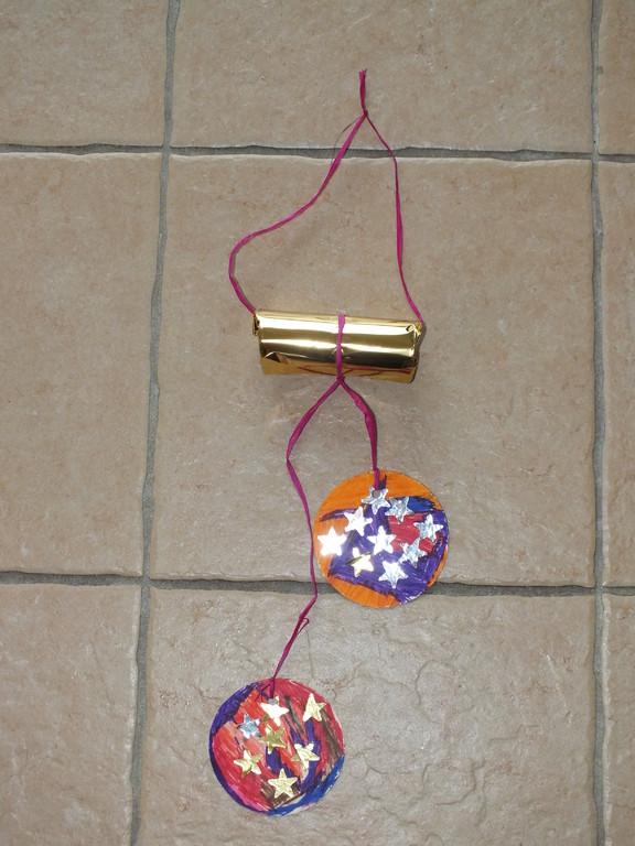 suspension boules de noël en carton décoré au feutre et gommettes, suspendues à un rouleau de papier WC recouvert de papier brillant, accroche en fil de rafia