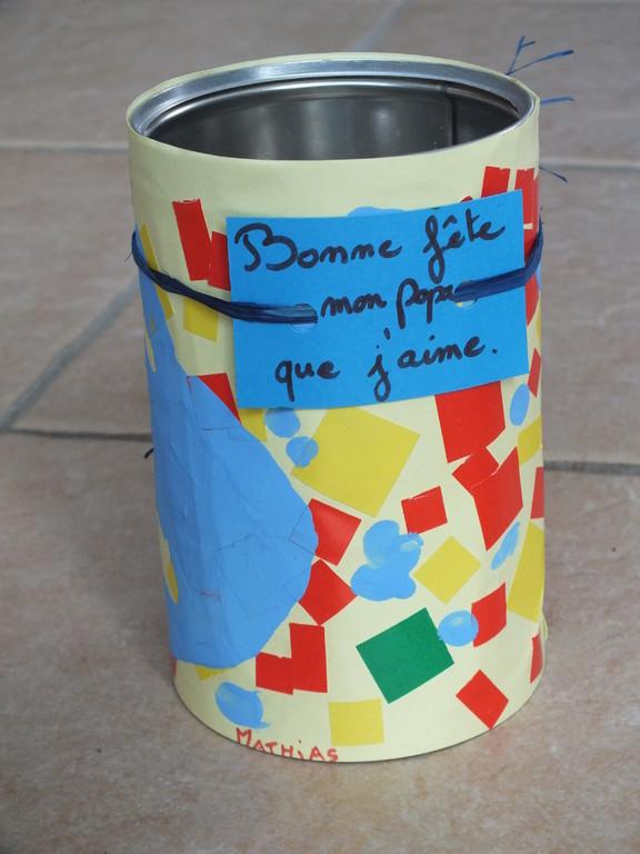 Pour la fête des pères : pot à crayons, avec boite en fer style café moulu, recouverte de feuille décorée par enfant de gommettes, et empreinte de mains et de doigts en peinture