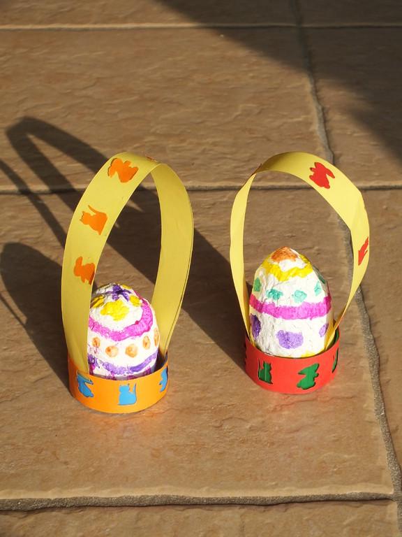 """panier oeuf de Pâques : oeuf en plastique tipe """"Kinder"""" recouvert de papier mâché, peint et vernis, mis dans un gros bouchon de lait décoré de papier couleur poinçonné"""