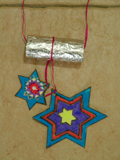 suspension étoiles de noël en carton décoré au feutre suspendu à un rouleau de papier WC recouvert de papier d'alluminium, accroche en fil de rafia