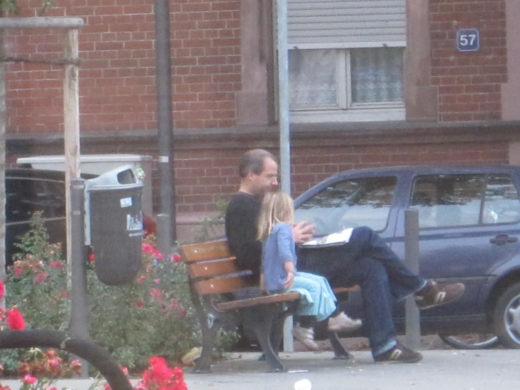 朝早くから公園で本を読んであげるパパ
