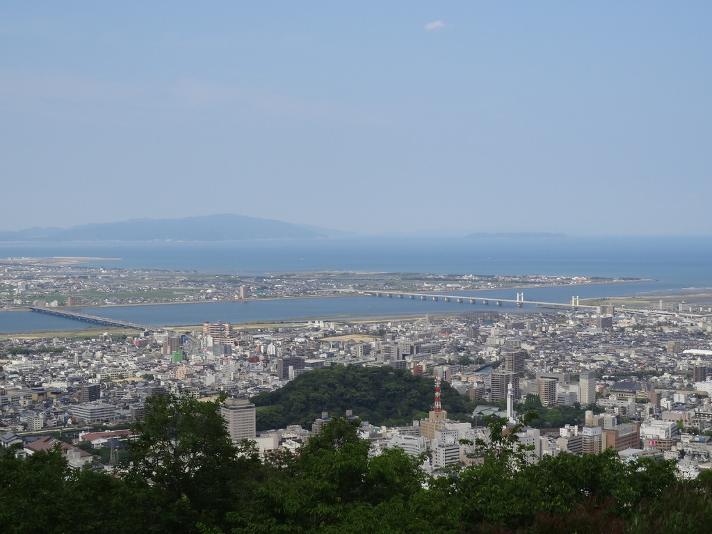 真ん中の緑のお山が城山(徳島城址)、高い塔は四国電力とNHK,川は吉野川、左の橋が吉野川大橋、右が阿波しらさぎ大橋、海の向こうが淡路島