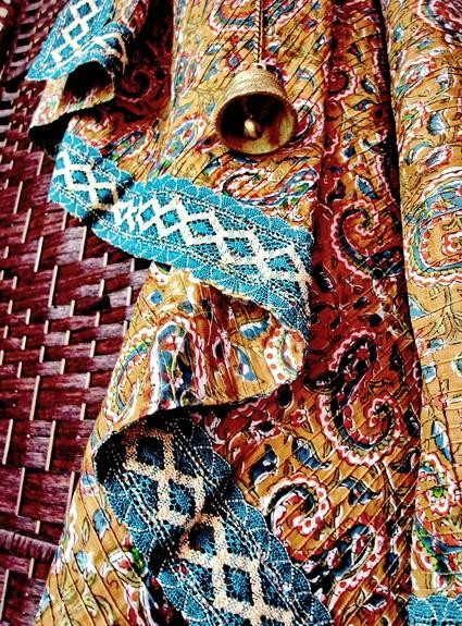 Mustard brown, pinched pleat, Indian cotton throw with green, paisley and vine print; close-up of teal-blue, silver-gold jari border