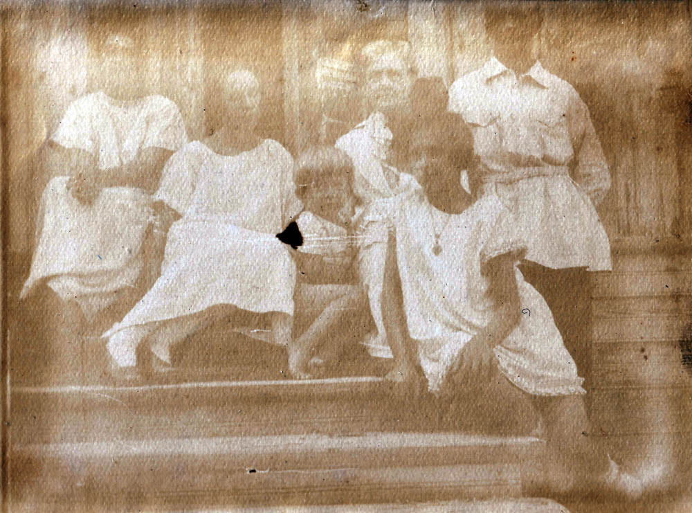 The Kogevin family sitting on the steps. Eugene (first on left), Mirik (fourth on left), Raissa (fifth), Kiev, 1925