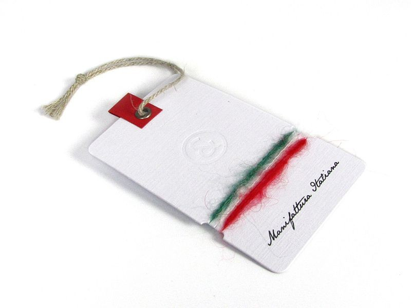Hangtag in denim textured off-white paper with logo engraved and wool tricolor yarns wrapped around