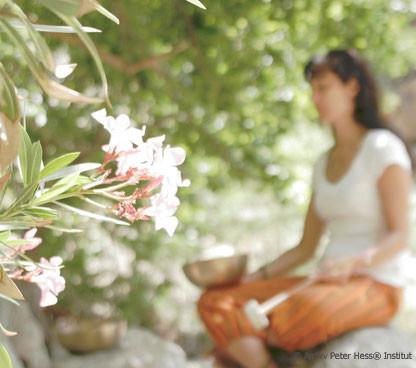 Frau meditiert mit Klangschale neben einem Orleanderbusch