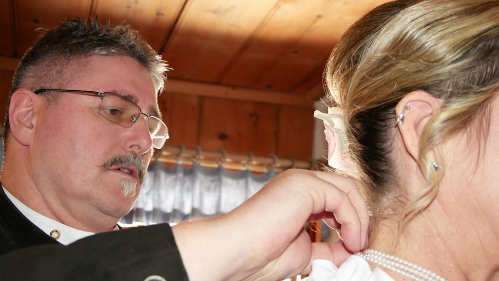 das Anlegen der Kette, also Halskette