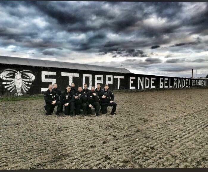 """Umstrittenes Foto: Polizisten posieren vor dem Spruch """"Stoppt Ende Gelände"""".Foto: Screenshot/Tsp"""