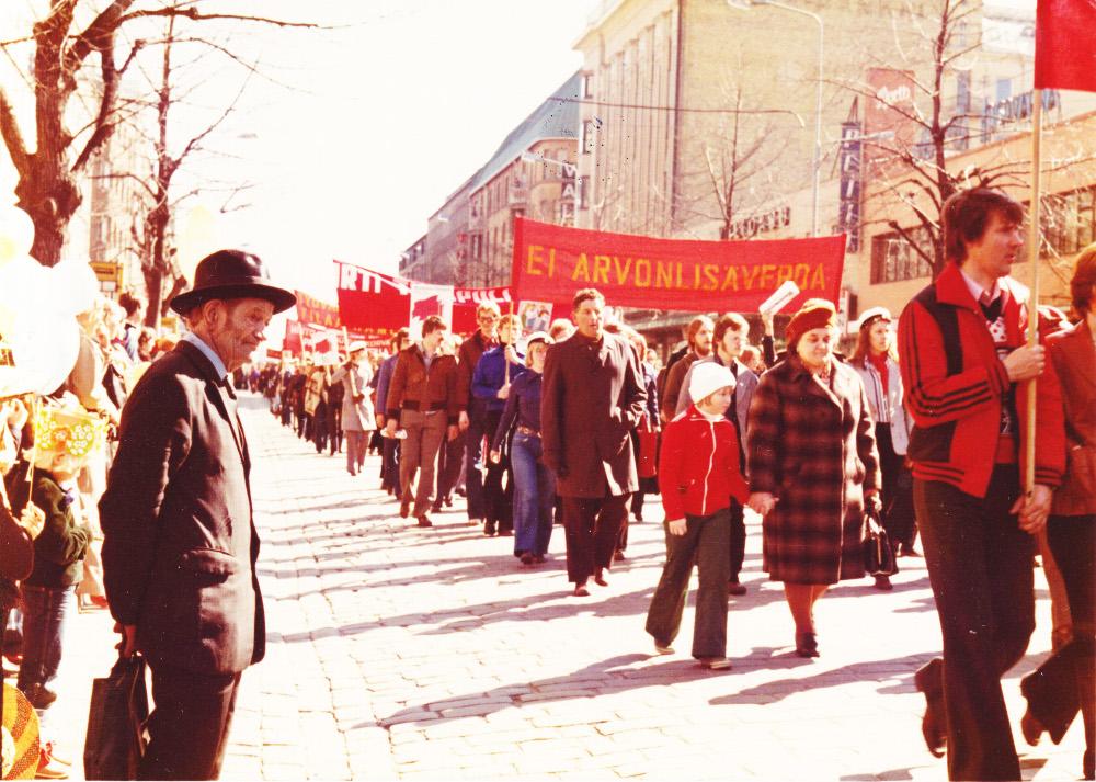 1. 70er Jahre in Tampere, Finnland: Kirsi an der Hand ihrer Großmutter bei ihrer ersten Mai-Demo im Leben. Copyright: Ilanga Films