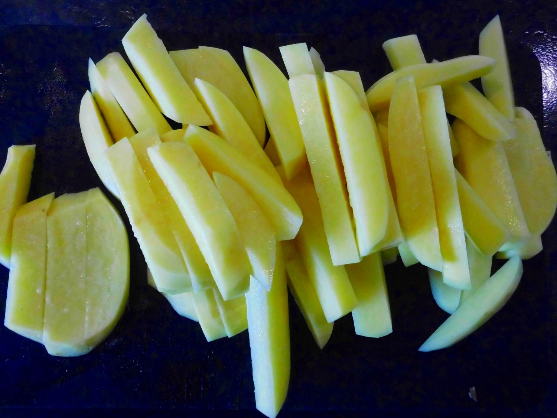 Die Kartoffeln in Spalten schneiden