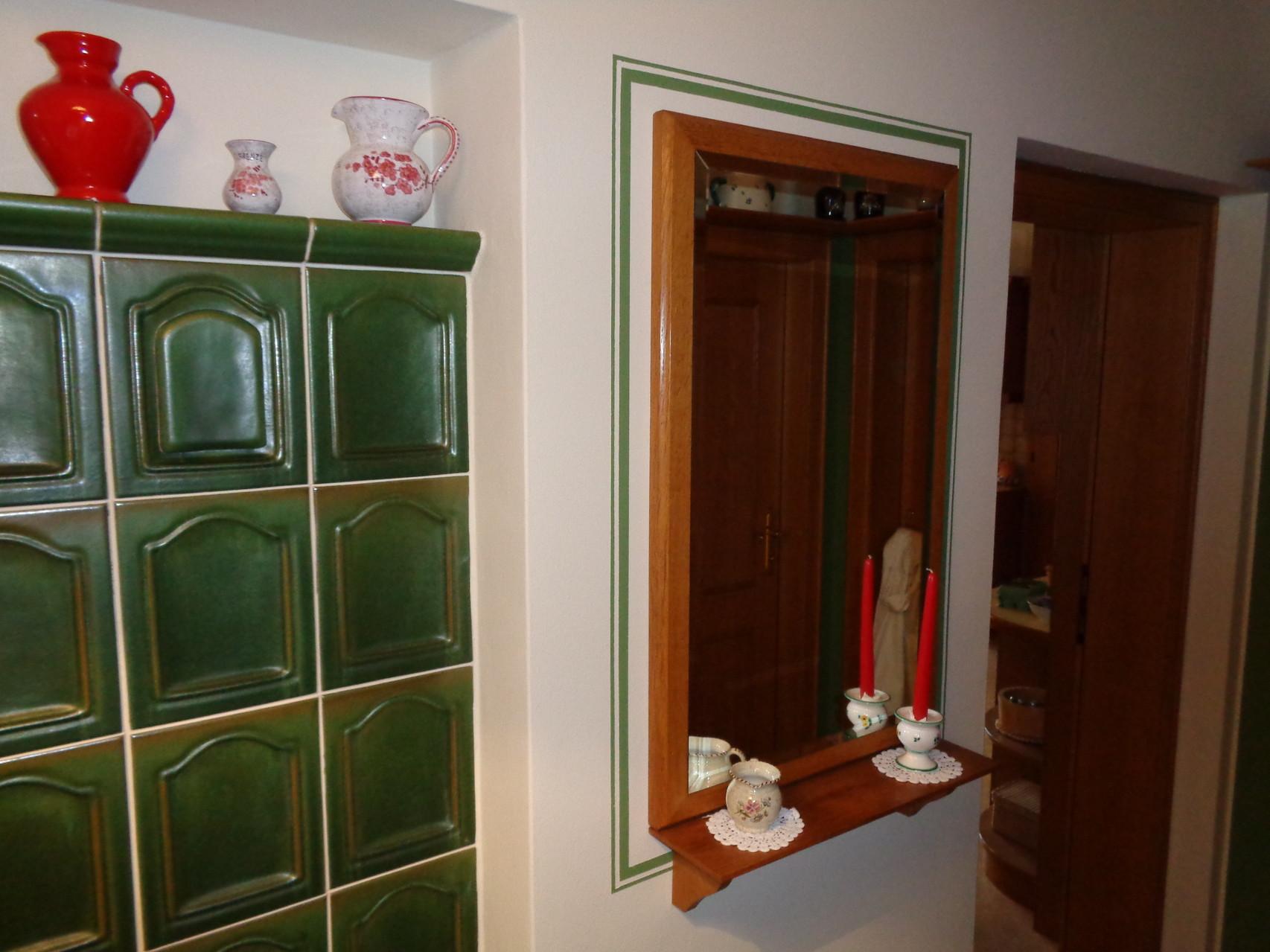 Umrahmung des Spiegels in den Farben des Kachelofens