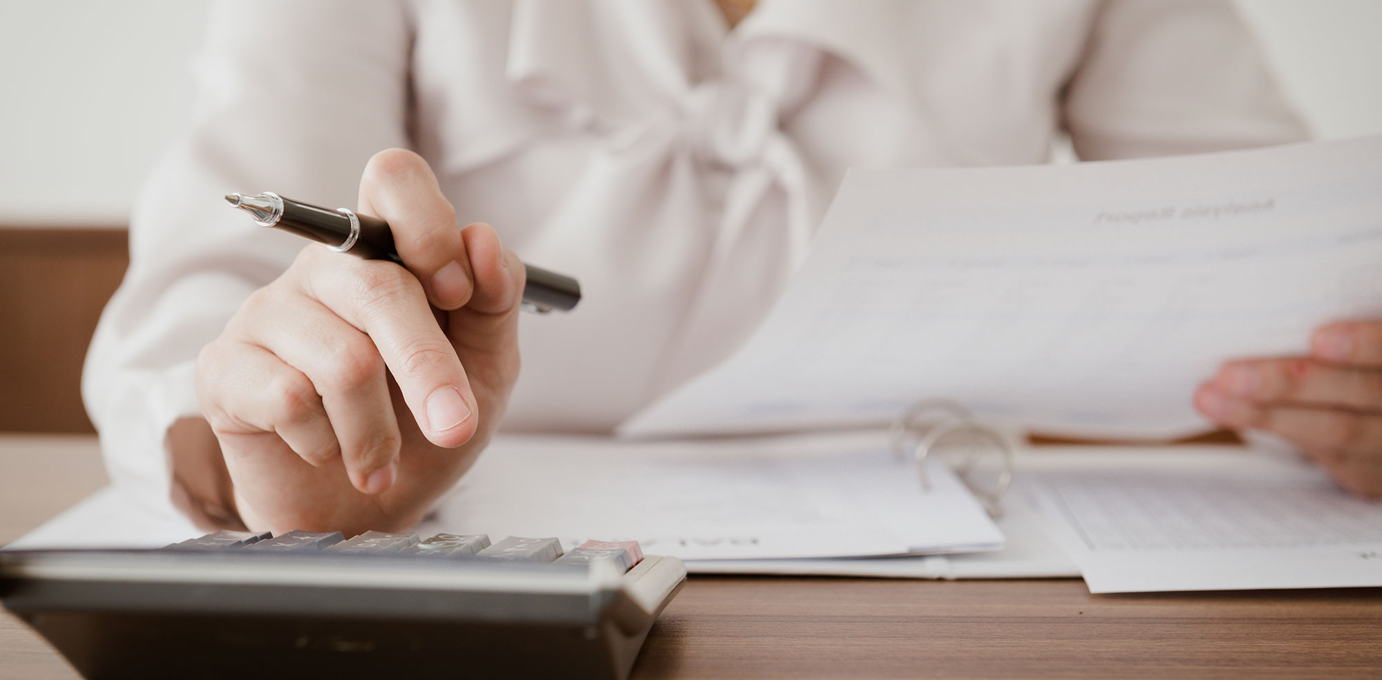 電卓をたたきながら書類作成の会計事務をする女性の仕事風景(手元)