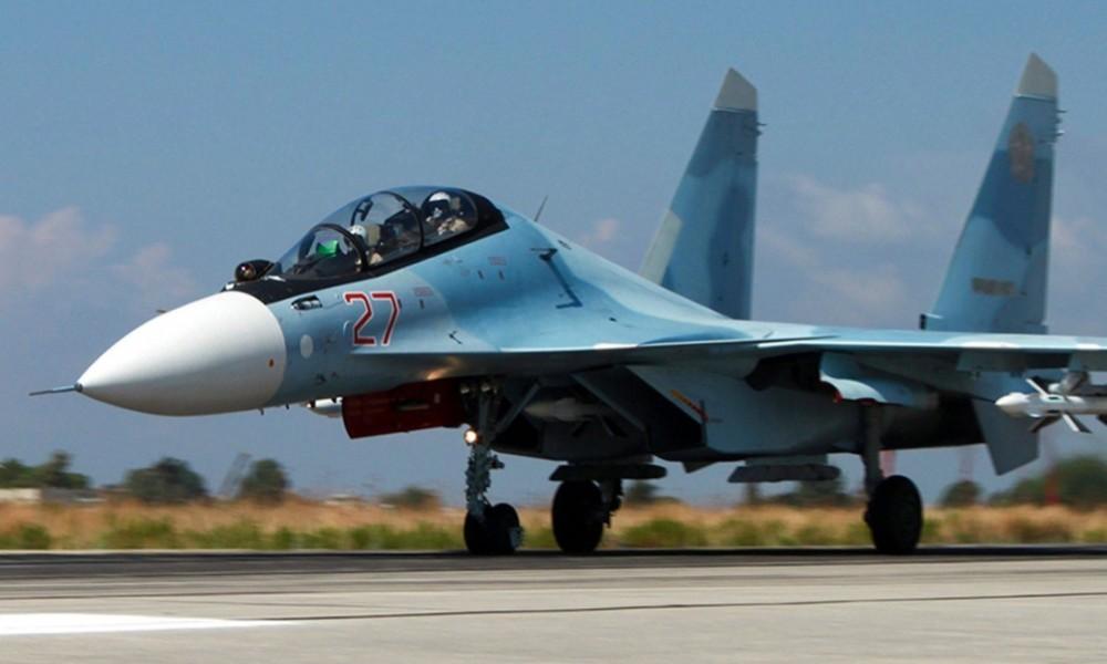 Un intercettore Su-30 in decollo da Latakia, da notare sulle derive i contrassegni della stella rossa e i  codici occultati. / © Reuters