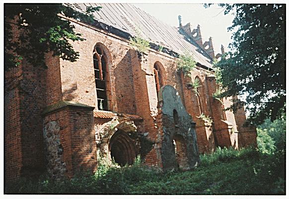Seitenschiff mit Eingangsbereich, man achte auf den Türbogen der nun wie ein Höhleneingang wirkt. Der Verbindungsbau zwischen Eingangsbereich und Haupteingangstür ist verschwunden. Es steht nur noch der Giebelrest.
