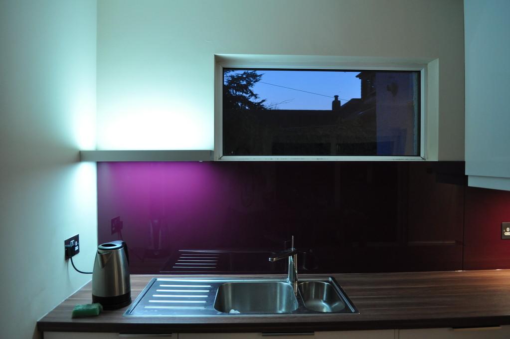 Painted back glass splashbacks with illuminated shelf