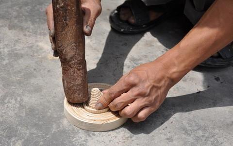 L'artisan finit sa galette de base en rentrant en force une pièce conique en lamelles de bambou, afin de maintenir et solidifier toute la structure.