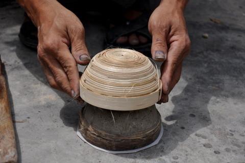 Cette structure étant encore souple, l'artisan la façonne à la main et lui donne son volume, avant de l'adapter sur un moule en pierre pour en régulariser les contours et obtenir la forme finale.