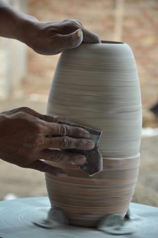 Après séchage, l'artisan ponce à nouveau à l'aide d'un tour.