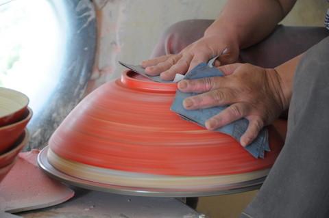 L'artisan passe une première couche de peinture ensuite poncée afin de préparer l'adhérence de la laque.