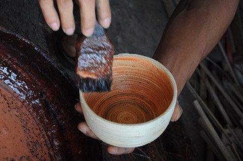 L'artisan applique la colle sur la pièce pour en fixer la forme.