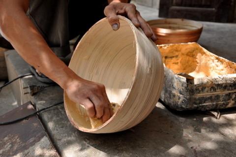 L'artisan enduit l'objet d'un mastic qui permet l'étanchéité entre les lamelles de bambou.