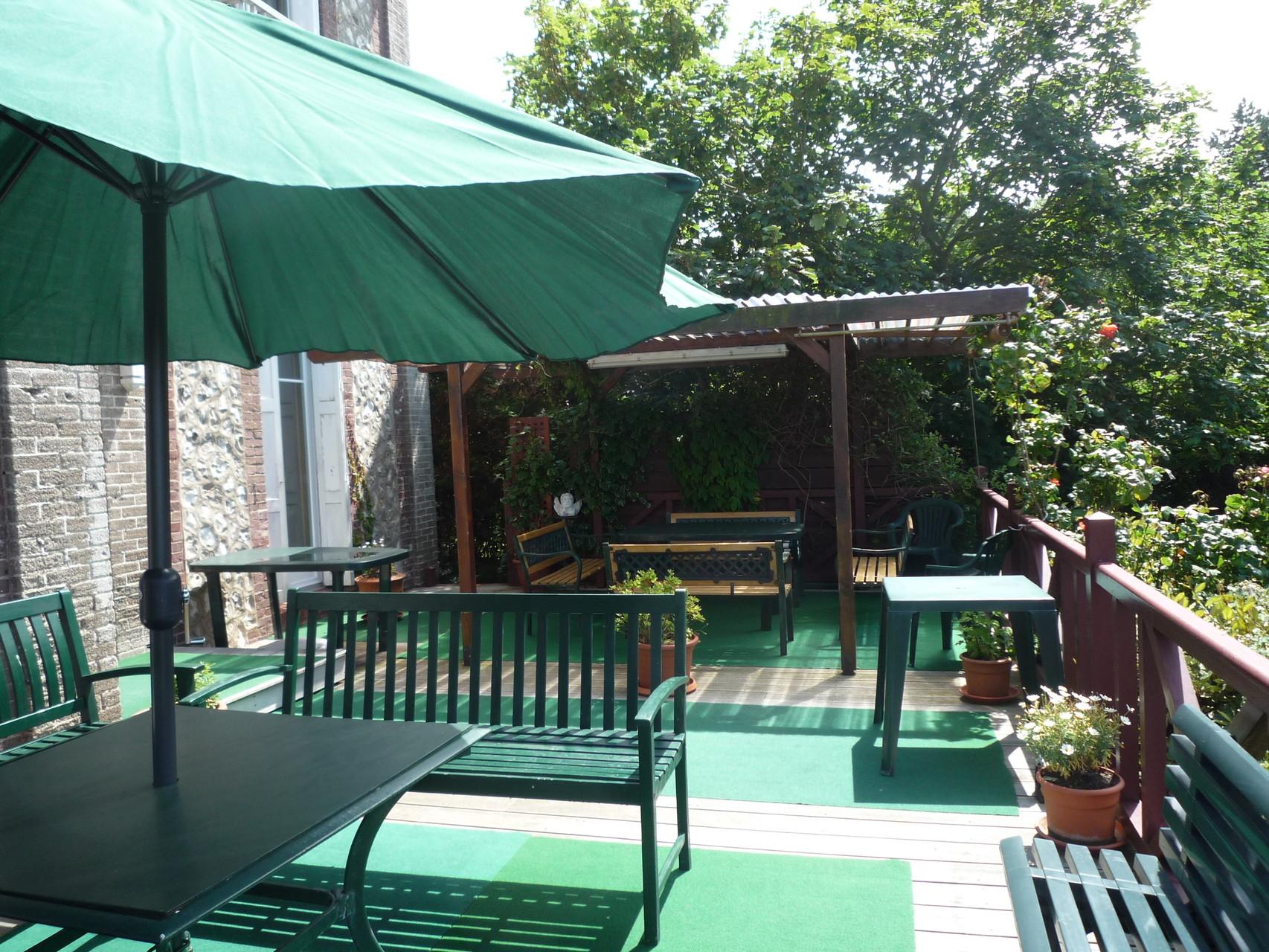 Salon et salle à manger de terrasse vus depuis les escaliers de la terrasse
