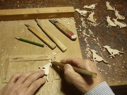 オリーブ材でイヌのブローチ手彫り中