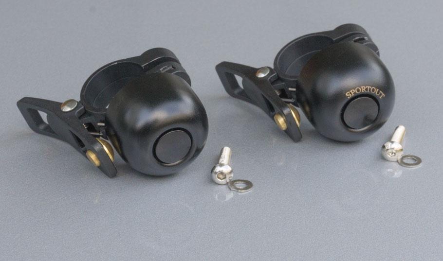 Zwei bis auf einen Schriftzug aeusserlich identische, kleine, schwarze Fahrradklingeln nebst Befestigungsmaterial