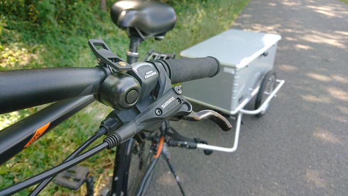Die kleine laute schwarze Fahrradklingel an einem schwarzen Lenker montiert.