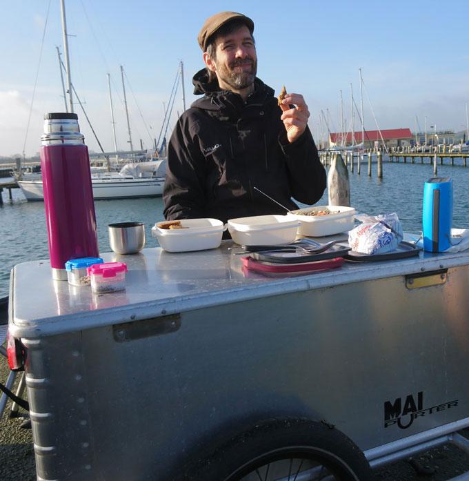Mann sitzt auf einem Bootssteg am Prototyp des Fahrradanhängers Maiporter Z130 und nutzt den Deckel seiner Box zum Essen als Tisch