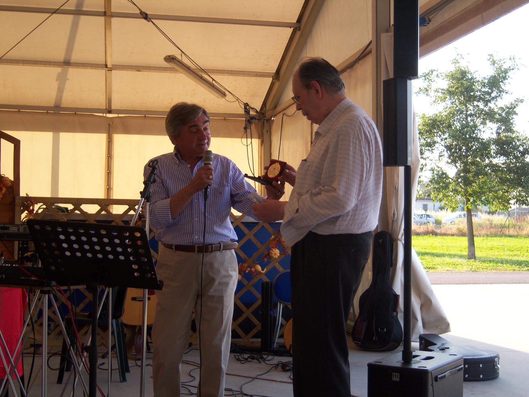 Wainer Mazza consegna a Giorgio Vezzani una medaglia AICA