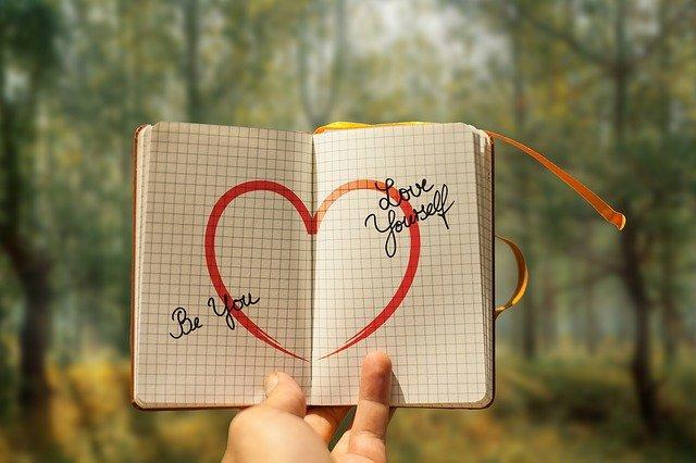 Hintergrund Wald, Notitzbuch aufgeschlagen, rotes Herz aufgemalt, Wörter Be You Love Yourself, von der linken Hand gehalten