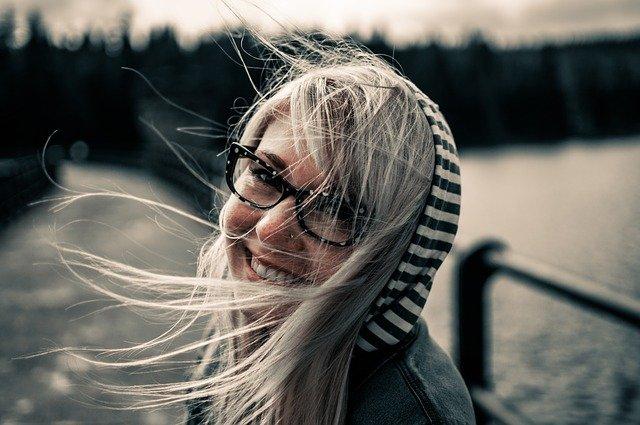 junge Frau, die Lacht, Haare wehen im Wind , sie schaut zur Seite ist in der Natur,Stress und Entspannung, EMDR, Trauma-Therapie, PTBS, Rosacea, Neurodermitis, Psoriasis, Psychotherapie