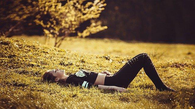 junge Frau liegt entspannt auf der Wiese