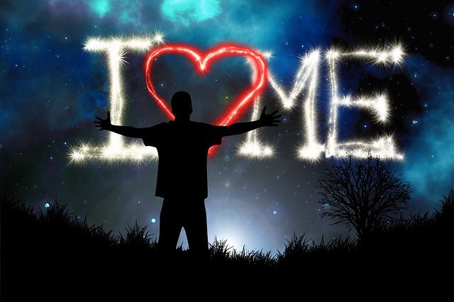 Mann steht mit ausgebreiteten Armen vor dem Abendhimmel, wo geschrieben steht: I love me