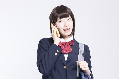 女の子がスマホから電話している画像