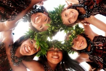 Lache nde hawaiiansiche Mädchen mit Blätter-Kopfkranz umarmen sich
