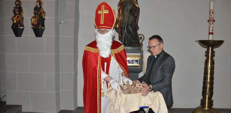 Bischof Nikolaus und Pfarrer Benedikt Fischer verteilen die Schokonikoläuse an die Besucher der Gaukirche © Sr. Theresita Maria Müller