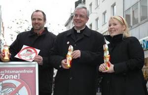 Die im Untertitel erwähnten Personen stehen in der Einkaufsstraße in Paderborn und halten jeweils einen Schokoladennikolaus in der Hand.