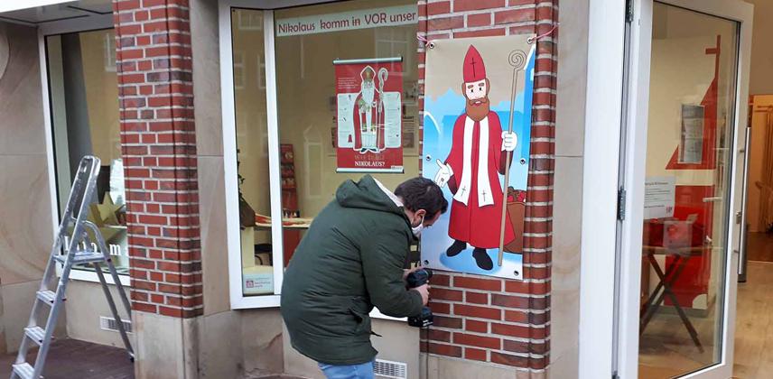 """Stephan Wendt befestigt die mit dem Heiligen Nikolaus bedruckte Plane an der Hauswand der Stadtpastoral """"Kirche in Meppen"""" © Sabine Kupper"""