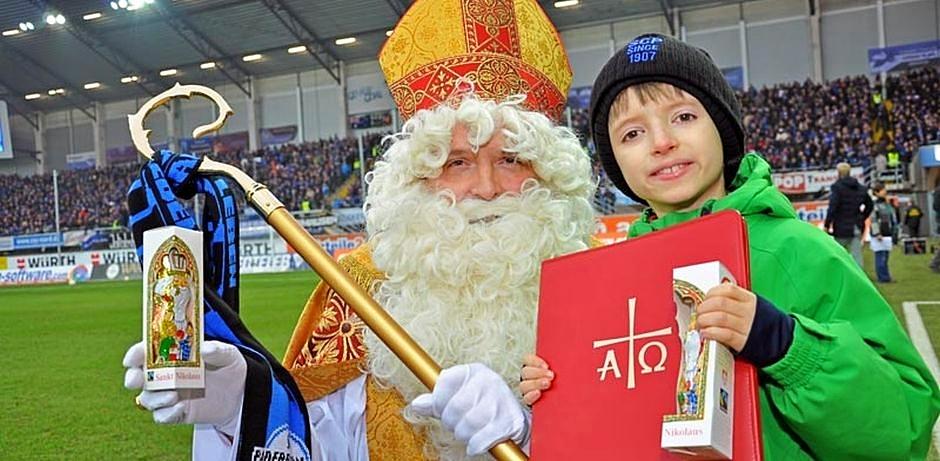 Der Nikolaus steht mit einem kleinen Jungen auf dem Spielfeld des Paderborner Stadions und hält einen Schokonikolaus in die Kamera.
