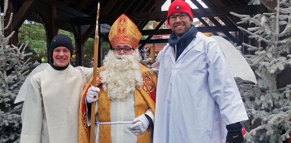 Der Nikolaus (mit Stab und Mitra) steht zwischen zwei als Engel verkleideten Jungen. Sie tragen ein weißes Gewand und Flügel auf dem Rücken.  Im Hintergrund sind links und rechts zwei Tannenbäume zu sehen.