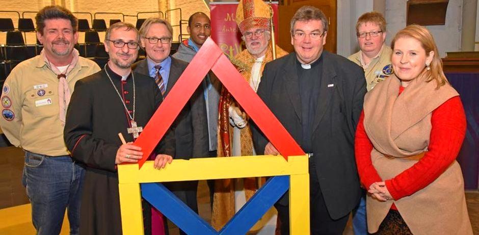 """Die im Untertitel erwähnten Leute stehen nebeneinander und schauen in die Kamera. Erzbischof Heße und Msgr. Austen halten ein aus bunten Holzteilen zusammengebautes """"Haus des Nikolaus"""" fest."""