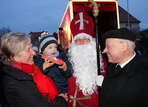 Der Nikolaus steht mit Passanten vor dem hell erleuchteten Coca-Cola-Weihnachtstruck.