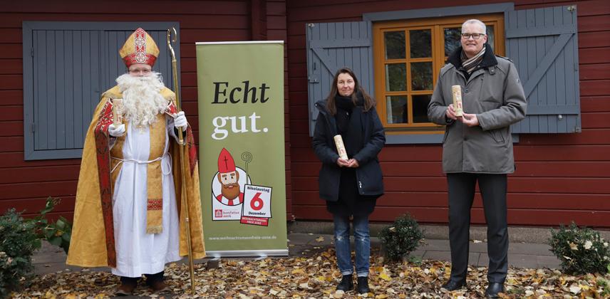 Bischof Nikolaus und der Vorsitzende des Diözesan-Bonifatiuswerkes in Hamburg, Michael Focke, überreichten die Schoko-Nikoläuse an Christiane Hartkopf von der Alimaus. (Foto: Valerie Wagner)
