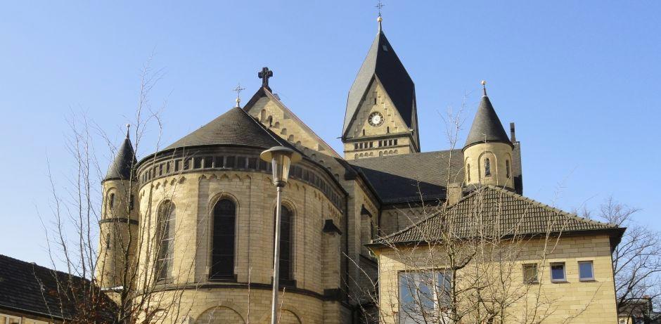 Vor blauem Himmel zeigt sich die dreischiffige neuromanische Kirche in Köln-Sülz