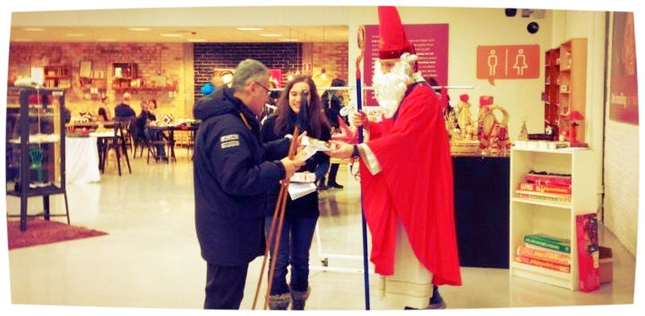 Der Nikolaus steht in einem Second-Hand-Geschäft in Schweden und verteilt Schokoladennikoläuse an Passanten.