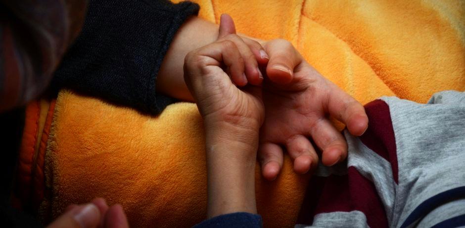 Auf einer gelben Kuscheldecke berühren sich die Hände eines kranken Kindes und dessen Mutter.