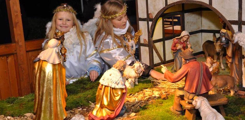 Zwei als Engel verkleidete Mädchen legen vorsichtig das Stroh für das Jesuskind in die Krippe. Rundherum stehen Figuren wie Hirten oder die Heiligen Drei Könige.