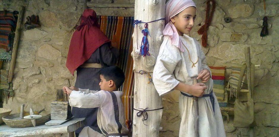 Im Vordergrund steht ein Mädchen mit Kopftuch - angelehnt an einen Holzpfahl. Im Hintergrund sitzt ein kleiner Junge an eine Holztisch und dahinter steht die Mutter, die einen Teppich webt. (Quelle: pixabay)